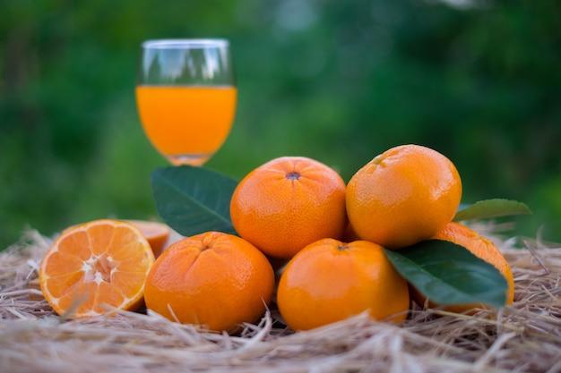 Sok pomarańczowy i owoce pomarańczy na drewnianym pudełku i słoma na rozmycie tła zielony bokeh. witamina c, żelazo, fosfor pomagają organizmowi dobrze wydalać.
