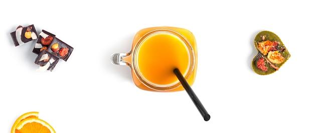 Sok pomarańczowy i słodycze z surowej czekolady z orzechami i owocami