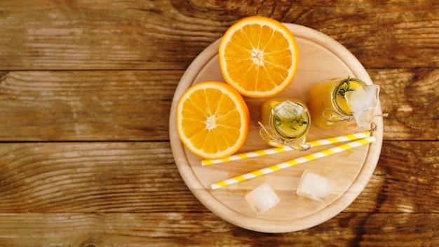 Sok pomarańczowy na drewnianej tacy. plasterki pomarańczy i kostki lodu