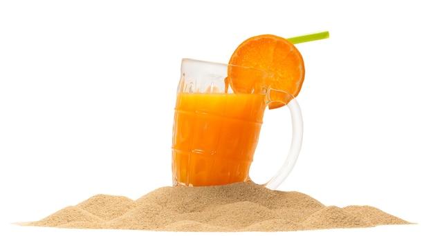 Sok pomarańczowy na piasku, na białym tle