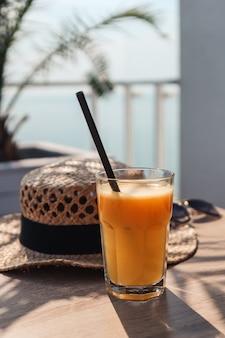 Sok pomarańczowy, słomkowy kapelusz i okulary w kawiarni na tle morza.