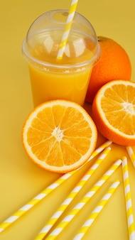 Sok pomarańczowy w fast food zamknięty kubek z rurką na żółtym tle. pokrojone pomarańczowe i żółte papierowe słomki na drinka. zdjęcie pionowe