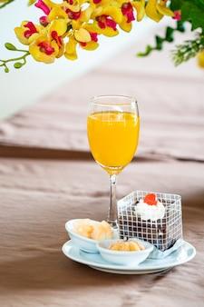 Sok pomarańczowy w kieliszku do szampana z ciastem i bagery obok.