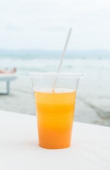 Sok pomarańczowy w szklance na plaży