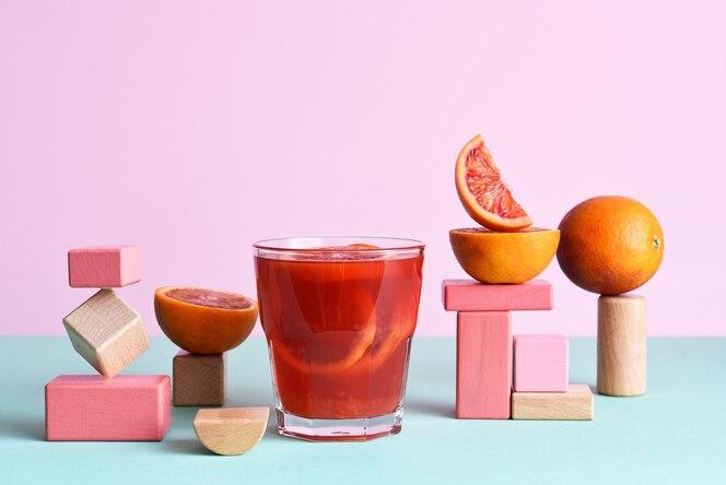 Sok pomarańczowy w szklance z geometrycznymi kształtami podim i pomarańczami na miętowym i różowym tle