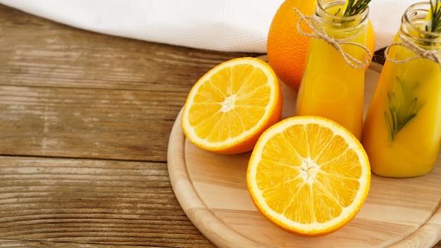 Sok pomarańczowy w szklanych butelkach. sok ozdobiony jest gałązką rozmarynu. sok na drewnianym tle z białym ręcznikiem
