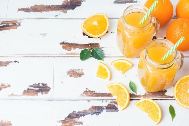 Sok pomarańczowy w szklanych słojach i świeżych pomarańczach na białym drewnianym nieociosanym tle.