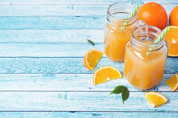 Sok pomarańczowy w szklanych słojach i świeżych pomarańczach na błękitnym tle.