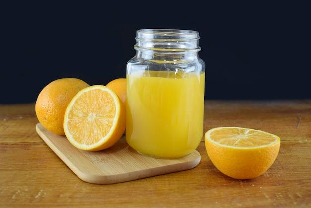 Sok pomarańczowy w szklanym słoju z pomarańczowymi plasterkami na drewnianym stole