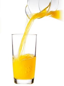Sok pomarańczowy wlewa się do szklanki z dzbanka