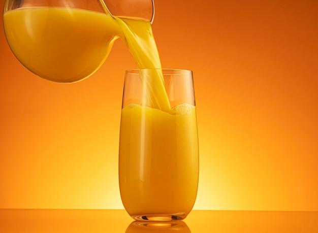 Sok pomarańczowy wlewający się do szklanki z rozbryzgami