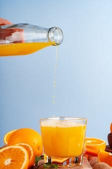 Sok pomarańczowy wylewa się z butelki do szklanki