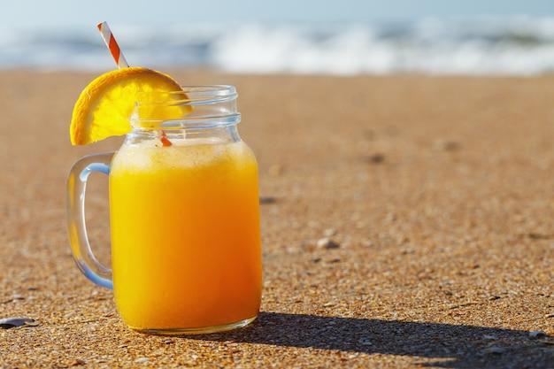 Sok pomarańczowy z miąższu na plaży z miejsca na kopię
