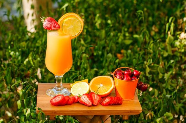 Sok pomarańczowy z owocami cytrusowymi, truskawką, wiśnią, deską do krojenia w czara, widok z boku.