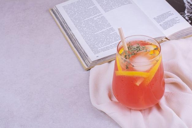 Sok pomarańczowy z plastrami owoców i przyprawami na białym stole.