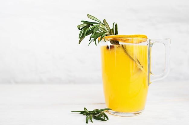 Sok pomarańczowy z rozmarynem na białym tle