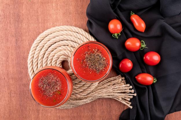 Sok pomidorowy na stojaku linowym i pomidory czereśniowe na czarnej tkaninie
