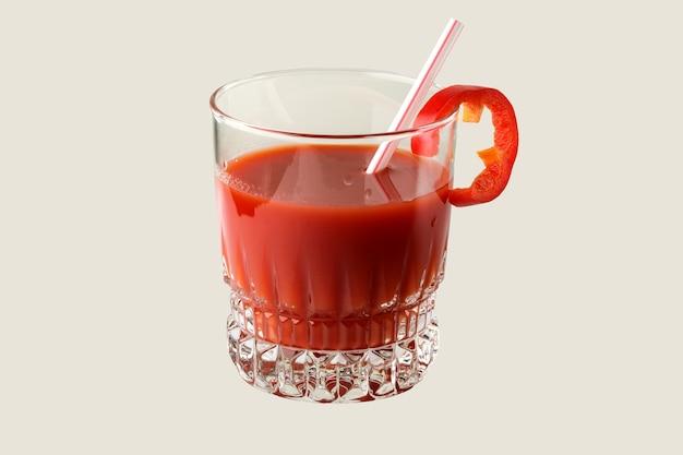 Sok pomidorowy w szklance z tubką koktajlową i plasterkiem słodkiej papryki z bliska na szarym tle