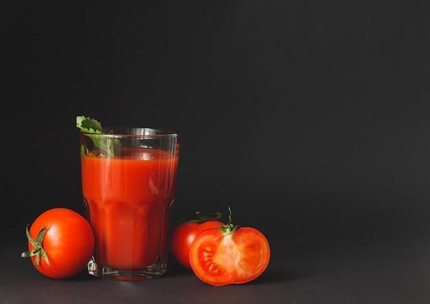 Sok pomidorowy w szklance ze świeżymi pomidorami na czarnym tle