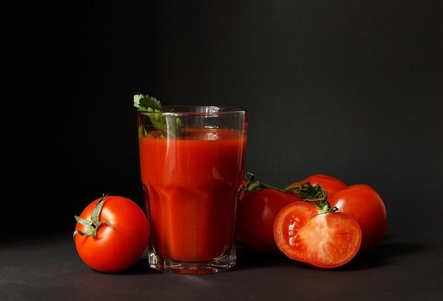 Sok pomidorowy w szklance ze świeżymi pomidorami wokół na czarnym tle