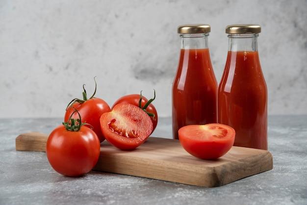 Sok pomidorowy w szklanych słoikach na drewnianej desce.