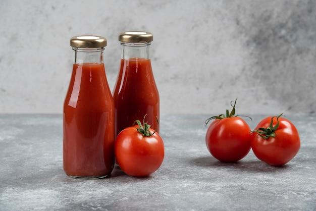 Sok pomidorowy w szklanych słoikach na tle marmuru.