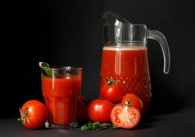 Sok pomidorowy w szklanym dzbanku i świeże pomidory na ciemnym tle