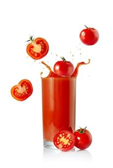 Sok pomidorowy z pomidorami i pluśnięcie na białym odosobnionym tle