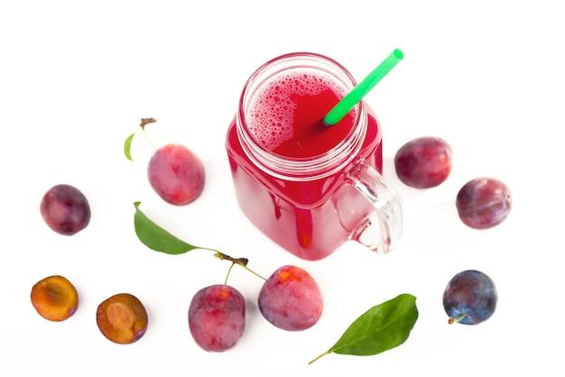 Sok śliwkowy w szklance ze świeżymi owocami śliwki na białym tle
