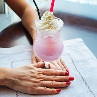 Sok truskawkowy shake na białym stole w restauracji z rękami kobiet