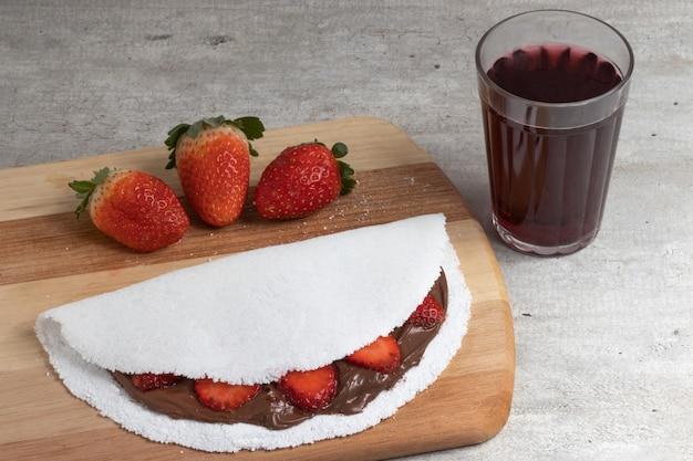 Sok winogronowy i sweet tapioca z orzechami laskowymi i truskawkami na stole do krojenia.