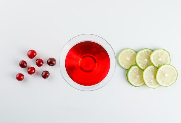 Sok wiśniowy w szklance z wiśniami, plasterki cytryny na białym tle