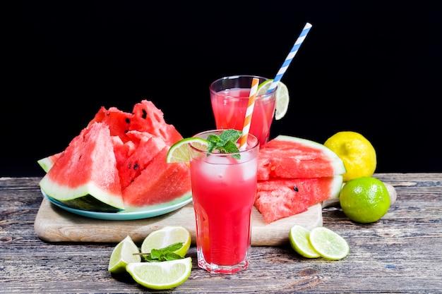 Sok z arbuza z dojrzałych czerwonych i soczystych arbuzów, czerwony sok to naturalny, zdrowy i dietetyczny produkt, sok z arbuza przelewa się do szklanego pojemnika