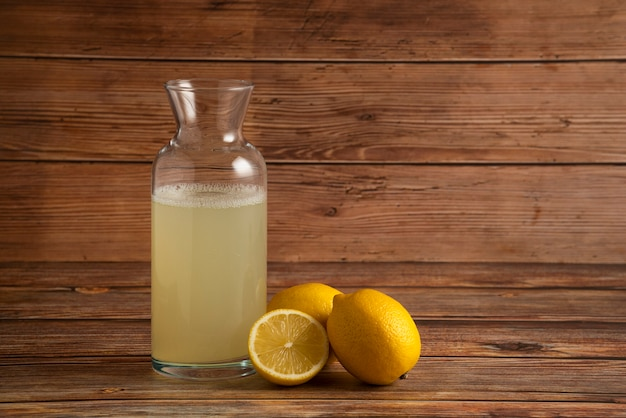 Sok z cytryny w szklanym pojemniku z owocami na drewnianym stole