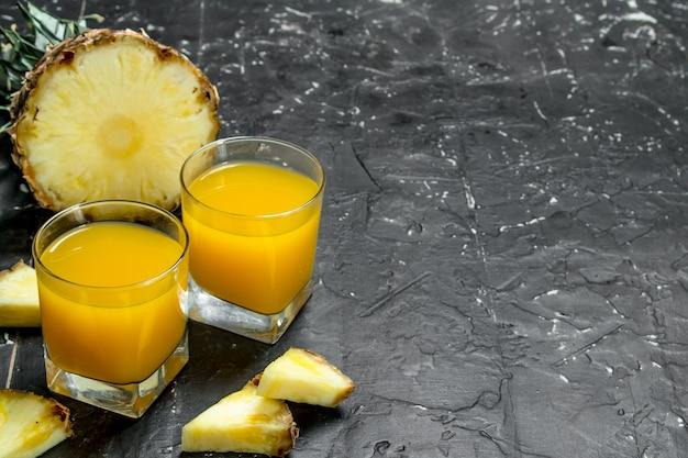 Sok z dojrzałych ananasów w szklance. na czarnym rustykalnym stole