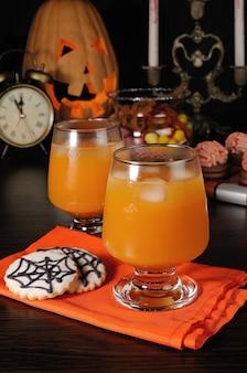 Sok z dyni z lodem na serwetce z ciasteczkami na halloween