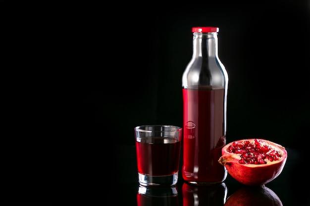 Sok z granatów w szklance, butelce i połowie granatu. witaminy, zdrowe jedzenie i picie.