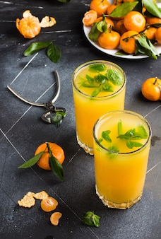 Sok z mandarynki w okularach w ciemności
