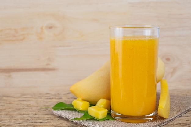 Sok z mango na drewnianym stole podłogowym.