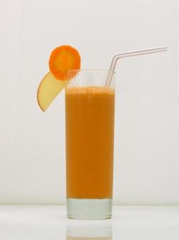 Sok z marchwi w szklance ze słomką i plasterkiem marchewki i jabłka napój na białym tle