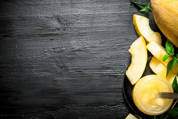 Sok z melona z listkami mięty. na czarnym drewnianym stole.
