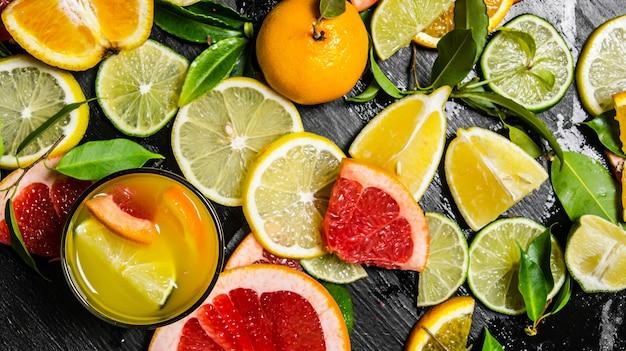 Sok z owoców cytrusowych. grejpfrut, pomarańcza, mandarynka, cytryna, limonka w szkle na czarnym drewnianym stole. widok z góry