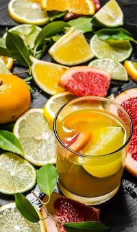 Sok z owoców cytrusowych. grejpfrut, pomarańcza, mandarynka, cytryna, limonka w szkle na czarnym drewnianym stole.