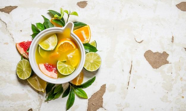 Sok z owoców cytrusowych - grejpfruta, pomarańczy, mandarynki, cytryny, limonki w filiżance z liśćmi