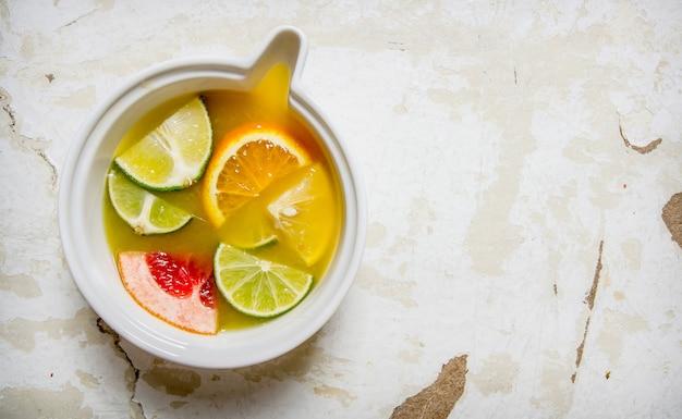 Sok z owoców cytrusowych - grejpfruta, pomarańczy, mandarynki, cytryny, limonki w filiżance