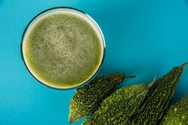Sok ziołowy z gorzkiej gurdy lub kareli to najlepszy naturalny lek na cukrzycę. całe gorzkie melony i szklanka pełna soku trzymane na kolorowym lub drewnianym tle. selektywne skupienie