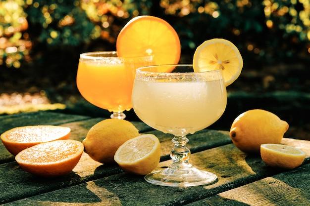 Soki pomarańczowe i cytrynowe w szklanym kubku na rustykalnym stole w parku