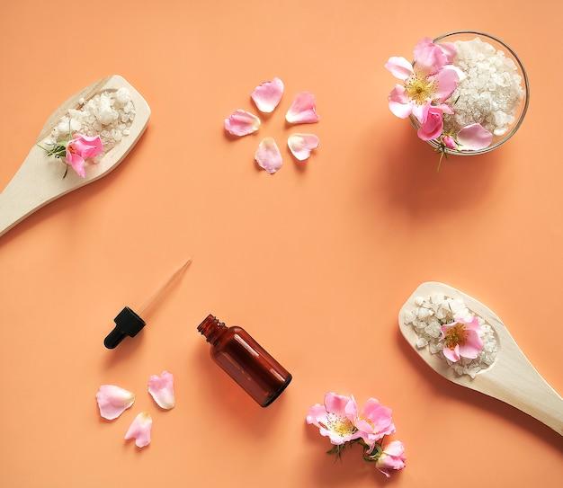 Sól do kąpieli w drewnianych łyżeczkach i szklanym słoiku z kwiatami i płatkami róż, na naturalnym beżowym tle. widok z góry.