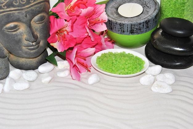Sól do kąpieli z różowymi kwiatami i posągiem buddy