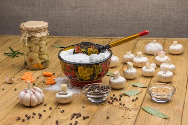 Sól do warzyw kiszonych słoik szklany z pieczarkami w puszkach świeże pieczarki posiekana marchewka i przyprawa na stole
